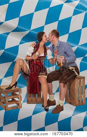 Young woman in the Dirndl flirts with man in leather pants sitting on wine boxes and Bavarian Diamond pattern in the background