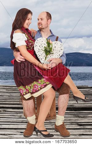 Young Bavarian couple in traditional costumes clothes sitting on a pier at the Lake and keep a white heart