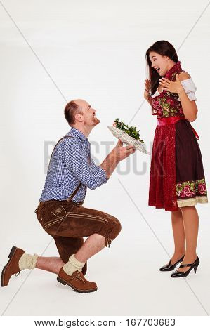 Young Bavarian man in leather pants makes his girlfriend in dirndl with a white heart a marriage application - isolated on white