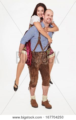 Image of a young Bavarian man carrying his girlfriend in dirndl piggyback - isolated on white