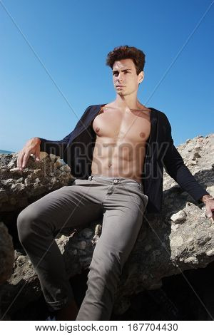 Outfits of a young man on a rock by the sea. A young boy is resting on a rock, a large rock, near the sea. The model wears an open shirt and pants. He has a well-defined physical and muscular.