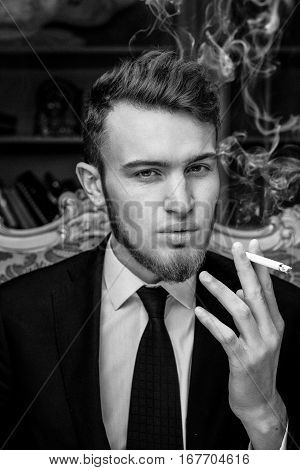 Close up portrait picture of a handsome young business man  smoking a cigarette black and white photo