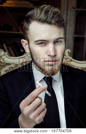 Close up portrait picture of a handsome young business man  smoking a cigarette