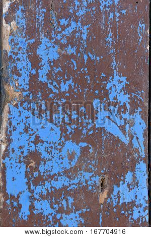 Traces of brown paint on an old wood painted blue