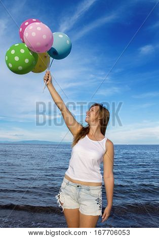 Girl with balloons on sea background. Festive air balloons and red hair girl. Pretty woman holding air balloons. Summer holiday picture. Colorful birthday decoration. Marine beach birthday greeting
