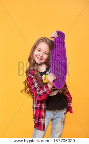 Beautiful teen girl with her birthday gift over yellow background. Happy preschool little kid holding brand new skateboard. Vertical portraot