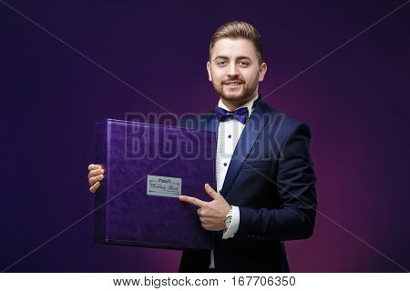 young photographer with a beard in a tuxedo holding a big wedding book and smiling on dark purple background