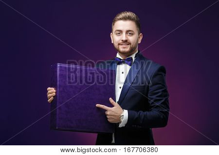 handsome young man with a beard in a tuxedo holds a large box and smiling on dark purple background