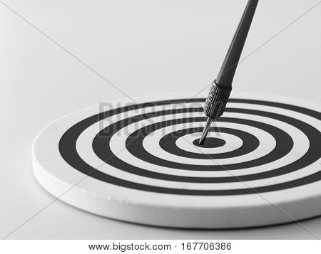 Black and white bullseye dart arrow hitting target center of dartboard. Concept of success target goal achievement. (selective focus)