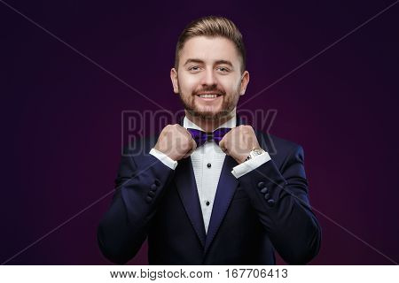 Handsome young man with beard in tuxedo and bow tie looking at camera. Fashionable and festive clothing. emcee on dark background