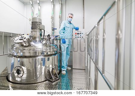 scientist is standing near big chromed tank in chemical factory