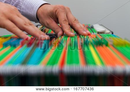 Abstract background of colorful hanging file folders in drawer. Male hands looking document in a whole pile of folders full of papers. Stock photo