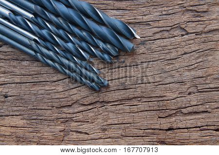 The closeup of many iron drill bit on the wood background