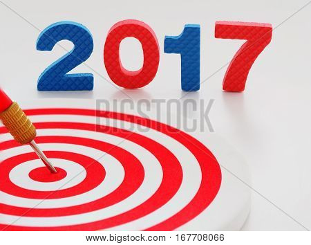 Year 2017 goal two thousand seventeen with red bullseye dart arrow hitting target center dartboard in background. Happy New Year.