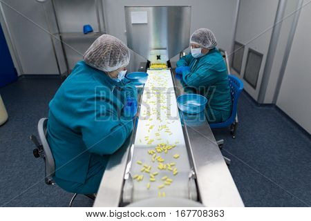 clean room two women in blue lab suits work on line with pills