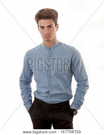 Model with blue shirt on a white background. A young man with a blue shirt with his hands in his pockets. White background. Stylish hair.