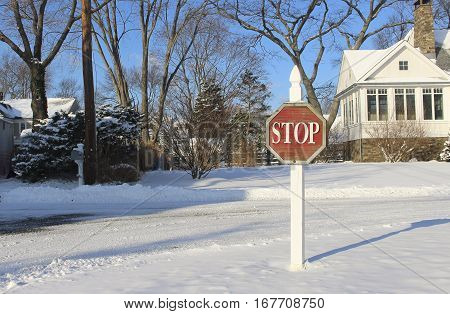 stop warning sign in the snow on a suburban street