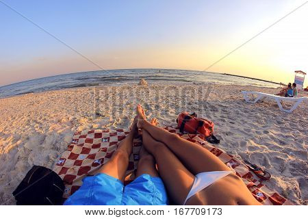Couple man and woman sunbathing on the beach overlooking the sea. They lie on a mat on the sand. In front of them a house of sand and water. Around other people are resting. Ukraine, Black Sea coast