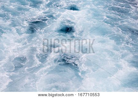Blue water background. Foamy wave on sea water made by cruise ship. Pacific ocean surf after motor boat. Splashes and drips of oceanic water. White water ornament on marine surface. Cruiseliner tail