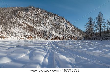 Winter road on the riverbed surrounded by rocks in South Yakutia Russia