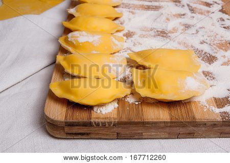 Close Up View Of Ready For Boiling Vareniki, Dumplings, Pierogi On Wooden Cutting Board With Flour..