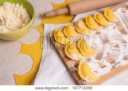 Close Up View Of Ready For Boiling Vareniki, Dumplings, Pierogi On Wooden Cutting Board With Flour A