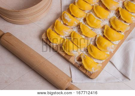 Ready For Boiling Vareniki, Dumplings, Pierogi On Wooden Cutting Board With Flour And Wooden Rolling