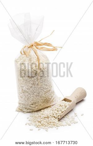 heap of white rice in transparent plastic bag with wooden scoop on white background.