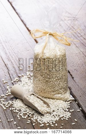 heap of white rice in transparent plastic bag with wooden scoop on table.