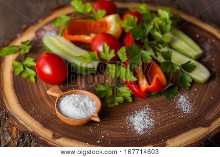 handcarved round wooden salter and vegetables on wooden background