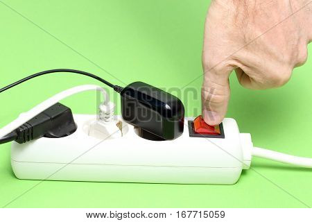 hand is switching off an electrical device with green background
