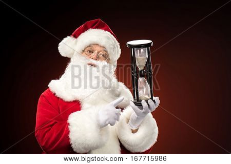 Santa Claus pointing on hourglass Christmas coming