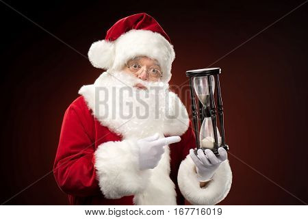Shocked Santa Claus pointing on hourglass Christmas coming
