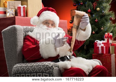 Happy Santa Claus sitting on grey armchair with wishlist in hands