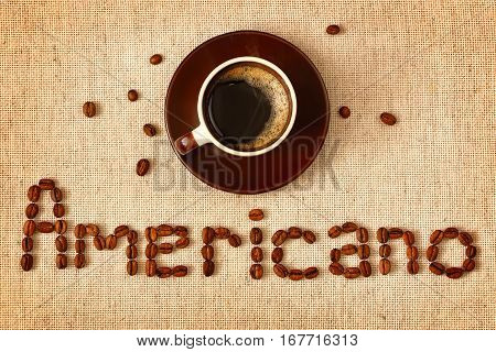 Hot cup of coffee and coffee beans on a background of cotton tablecloth