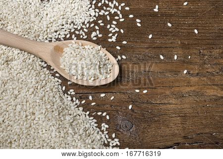 heap of white rice in wooden spoon on table.