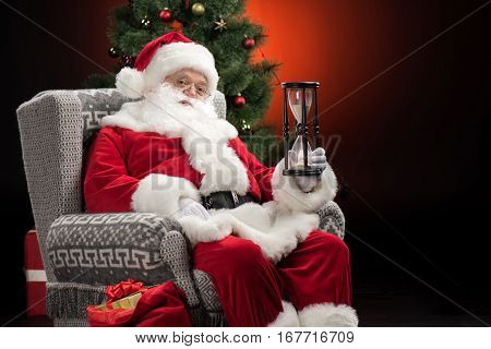 Santa Claus sitting in armchair and showing sandwatch