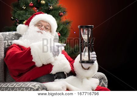 Santa Claus sitting and pointing at hourglass