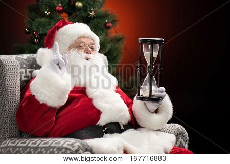 Santa Claus sitting in armchair with hourglass and gesturing Christmas coming
