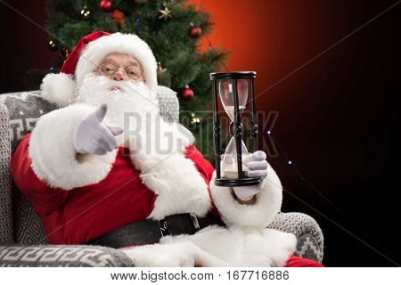 Santa Claus sitting with hourglass and pointing at camera Christmas coming