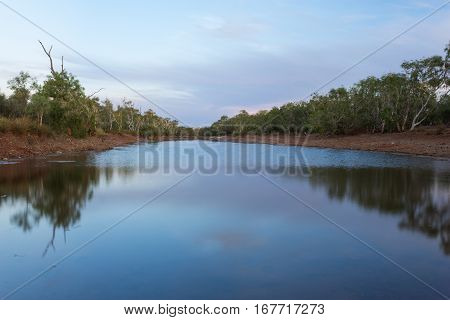 Australian outback waterhole during sunset - Pilbara region of Western Australia, Australia.