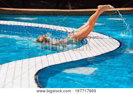 Funny girl swimming and diving in blue pool with fun - jumping deep down underwater with splashes. Family lifestyle children water sports activity and swimming lesson on summer holiday.