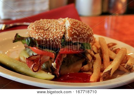 Scrumptious bacon cheeseburger with a side of crispy French fries  and pickle on simple white plate on table at restaurant.