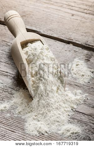 heap of white flour in wooden scoop on table.