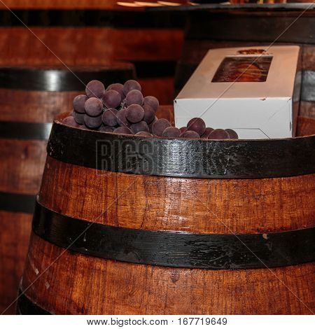 Grapes And Bottle Box On Fine Big Wine Wooden Barrel