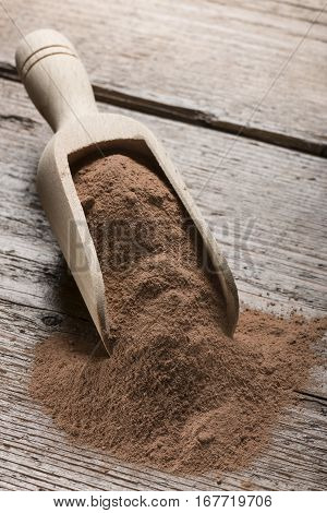 heap of cocoa powder in wooden scoop on table.