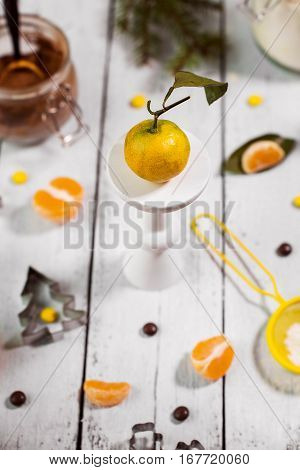 fresh tangerines with leaves on a wooden stander with Christmas decorations