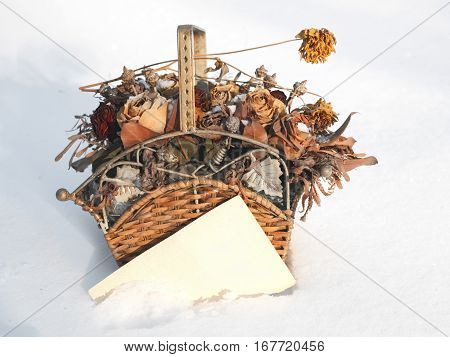 Bunch of beautiful flowers in a wicker basket on the snow with a blank paper for text and design