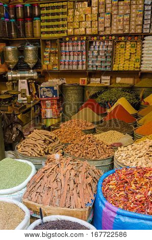 Huge barrels of colorful herbs and spices stacked in little shop in souks of Fez, Morocco, North Africa.
