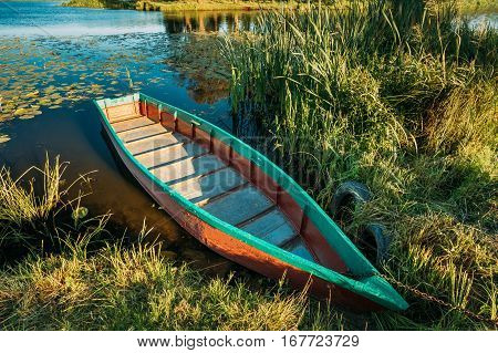 Lake Or River And Old Wooden Blue Rowing Fishing Boat In Grass At Rivers Bank At Beautiful Summer Sunny Day Or Evening.